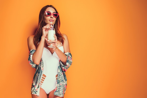 Woman in swimsuit holding beverage