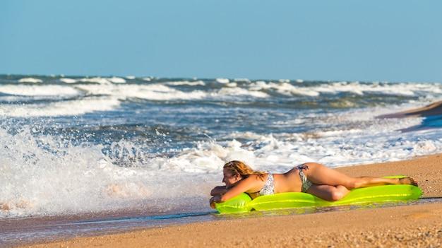 Woman in a swimsuit lies on an air mattress