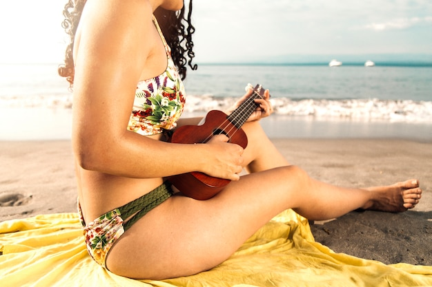 Woman in swimsuit playing ukulele on beach