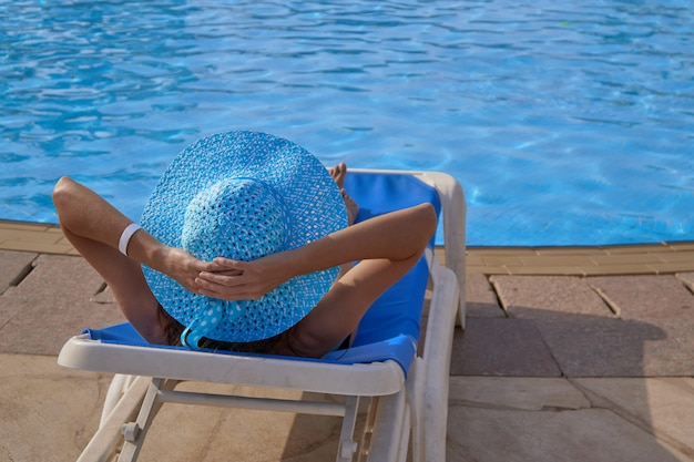 Woman in swimsuit relaxing on chaise-longue on the edge of the swimming pool