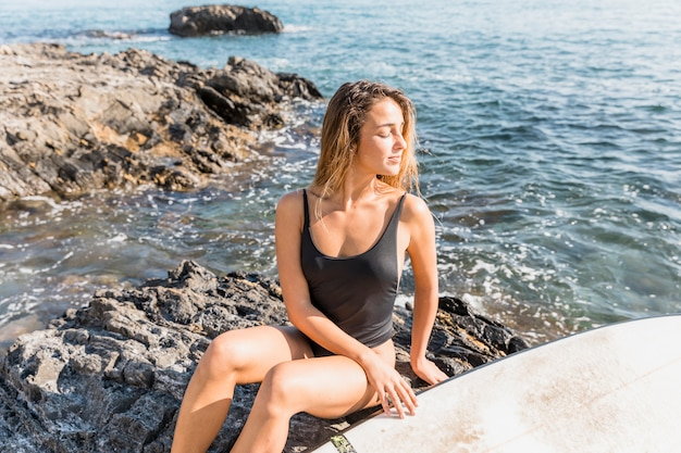 Woman in swimsuit sitting on rocky sea shore with surfboard