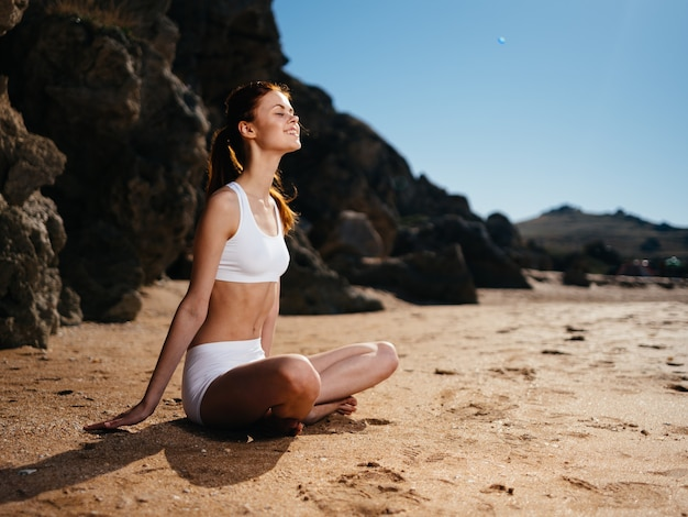 Woman in a swimsuit sitting on the sand meditation fresh air island vacation