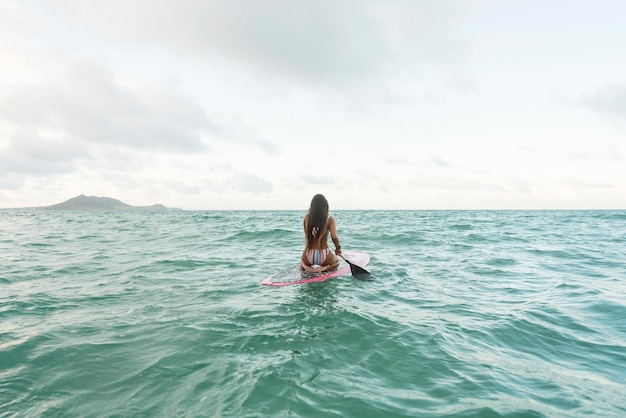 Woman in swimsuit surfing in hawaii