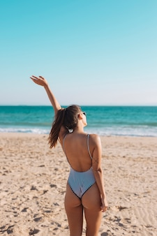 Woman in swimsuit waving hand on seaside
