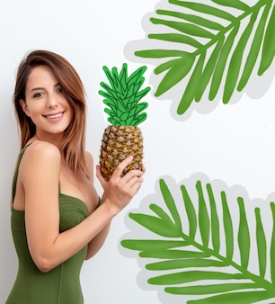 Woman in swimsuit with pineapple