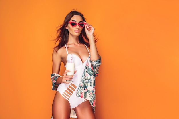 Woman in swimsuitolding beverage