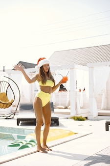 Woman in swimwear and christmas hat holding glass and drinking cocktail near swimming pool.