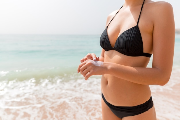 Woman in swimwear is applying sun cream on her hand with her finger at the sea background.
