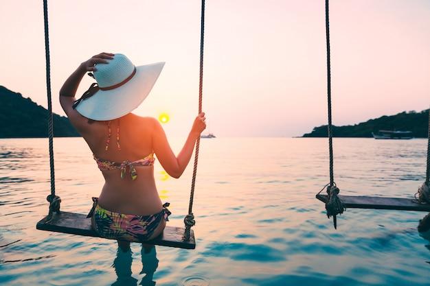 Woman on swing in the sea on tropical island