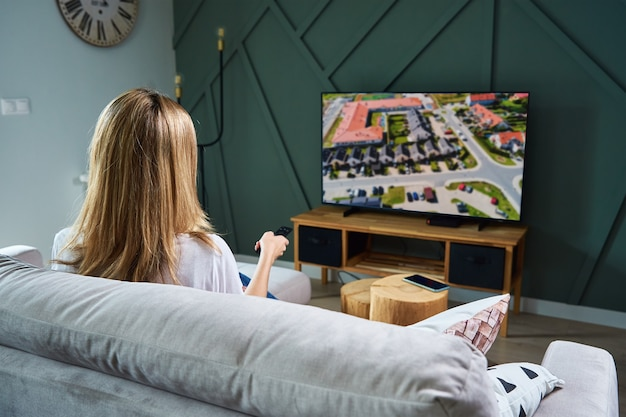 Woman switch channels on tv set with remote control.