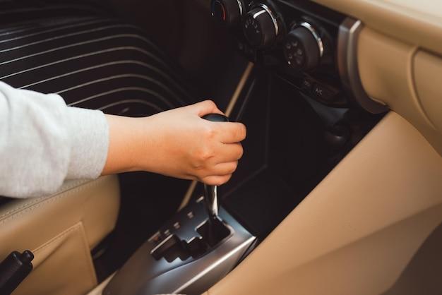 Женщина переключает акпп крупным планом. крупный план водительского адм включает режим drive на рычаге коробки передач акпп деталей салона автомобиля