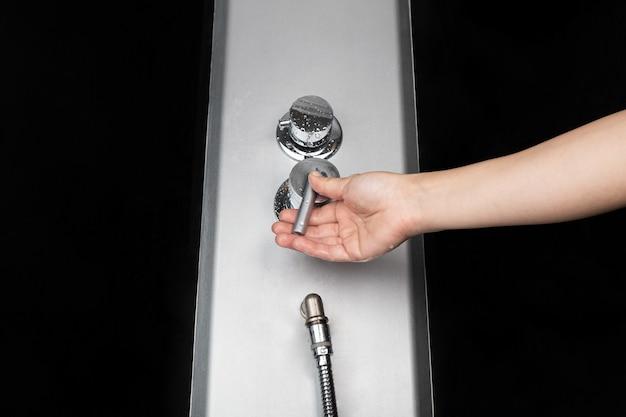 女性はシャワーのミキサーを冷水と温水のクローズアップで切り替え、体の衛生のために水道水をオンにします。