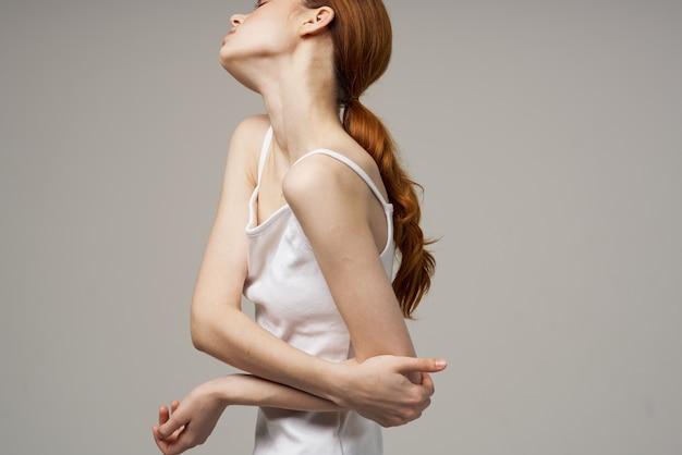 Женщина в футболке перемещает руку в сторону локтя эмоция боль