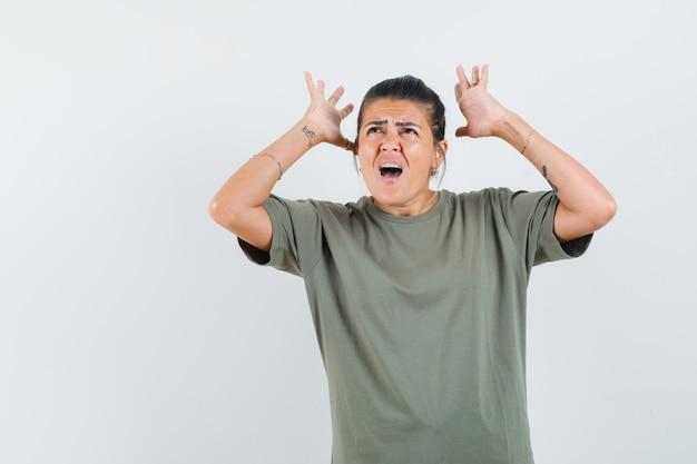 Donna in maglietta alzando le mani e guardando agitato