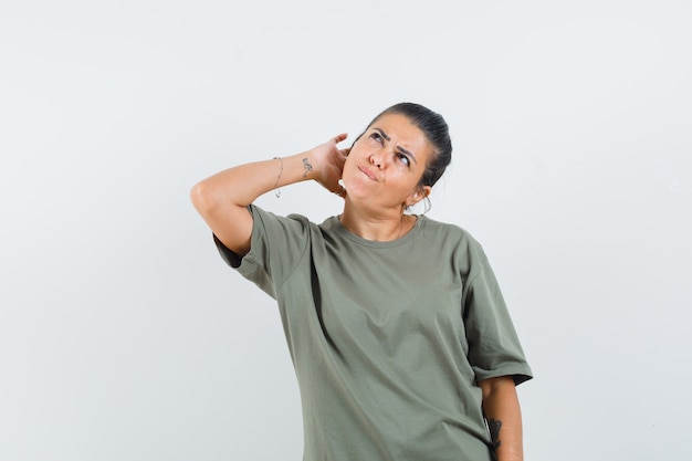 Woman in t-shirt scratching head and looking indecisive