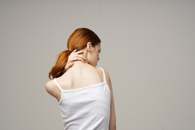 Woman t-shirt touches her back with hands