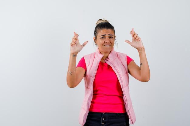 Donna in t-shirt, gilet che tiene le dita incrociate e sembra speranzosa