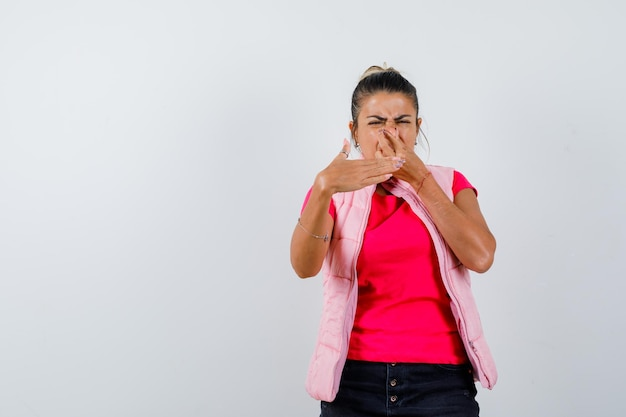 Donna in maglietta, gilet che si pizzica il naso a causa del cattivo odore e sembra disgustata