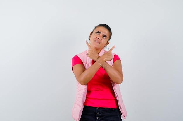Donna in t-shirt, gilet che punta le dita verso l'alto e sembra speranzosa