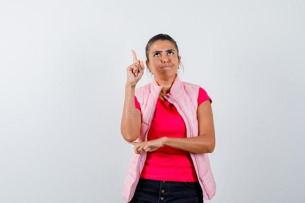 Donna in t-shirt, gilet che punta in alto e sembra seria