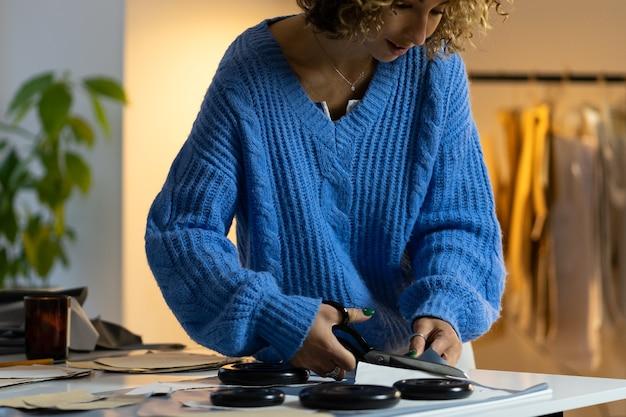 여성 재단사는 의류 공장 디자인 스튜디오 아틀리에에서 패턴 초안 용지의 의류 샘플을 잘라냅니다.