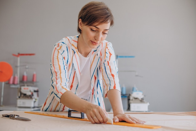 Woman tailor drawing sketch on fabric