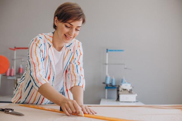 生地にスケッチを描く女性の仕立て屋