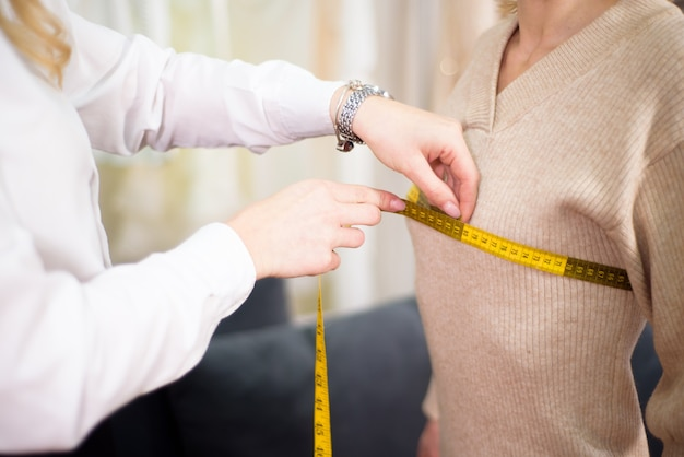 モデルの女の子と測定を行う女性のテーラーファッションデザイナー。コンセプトは服を縫います。
