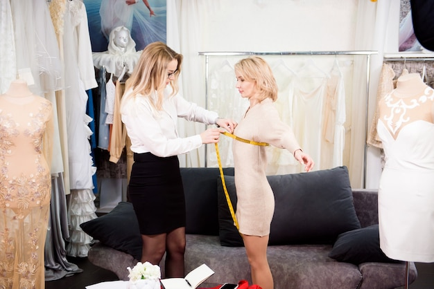 Woman tailor fashion designer taking measurement with model girl. concept sew clothes.