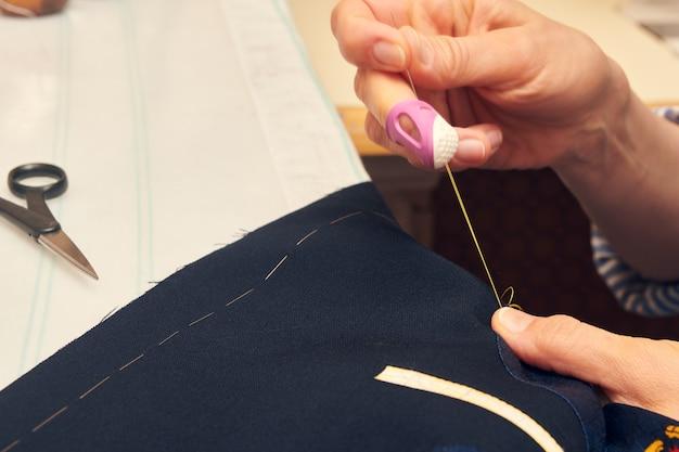 作業台に座っている間、針と糸で縫製ジャケットに包まれた女性の仕立て屋。カスタムメイドのジャケットの仕立てのスーツ。オーダーメイドのスーツ仕立て。
