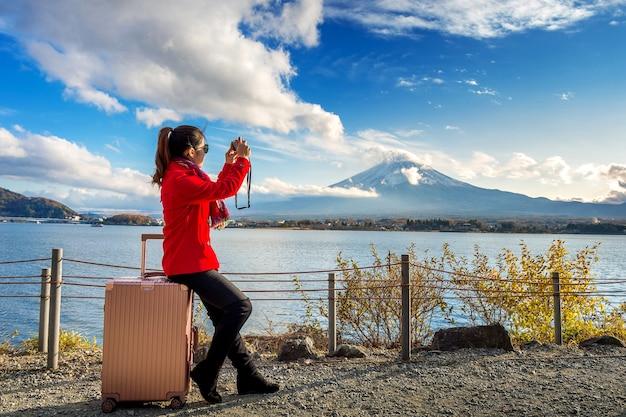 Женщина делает снимок в горах фудзи. осень в японии. концепция путешествия.