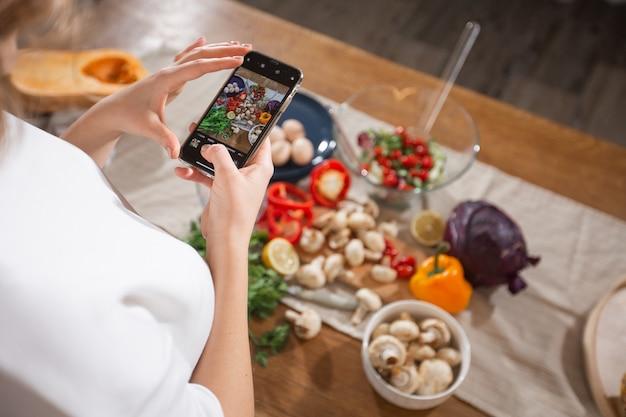 女性は彼女のキッチンで携帯電話でさまざまな美しい野菜や野菜の写真を撮ります。スマホ食品写真。健康的な食事、ベジタリアン料理、ダイエット。減量とデトックスのために。