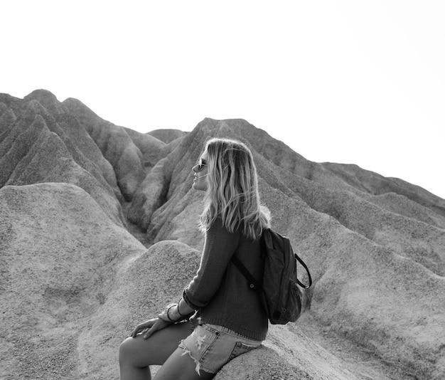 女性は岩の上でのハイキングから休憩します