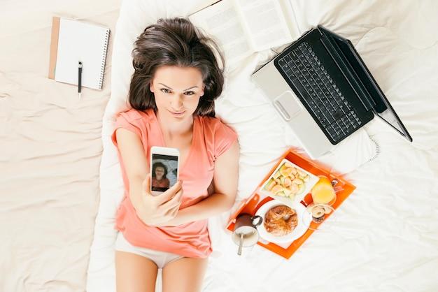 Женщина делает селфи с телефоном и завтракает. она в спальне