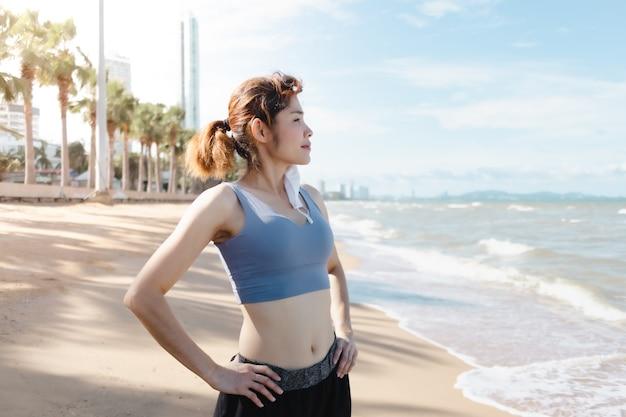 Женщина снимает маску и отдыхает после завершения пробежки по пляжу летом