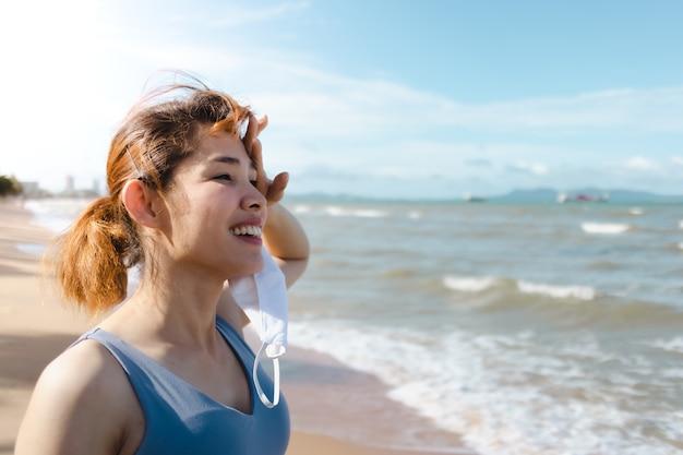 여름에 해변에서 조깅을 마치고 마스크를 벗고 휴식을 취하는 여성