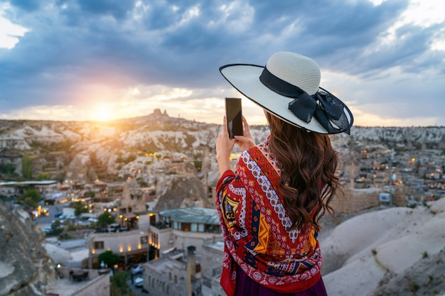 Woman take a photo with her smartphone at goreme, cappadocia in turkey.