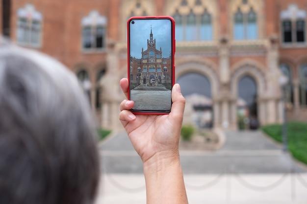 여자는 바르셀로나의 허술한 건물에 스마트 폰으로 사진을 찍습니다. 여행자, 관광, 발견, 백인 여성