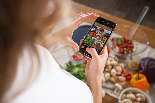 Woman take a picture of different beautiful vegetables and greens with a mobile phone at her kitchen. smartphone food photography. healthy eating, vegetarian food, dieting . for weight loss and detox.