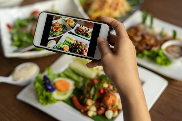 Женщина фотографирует еду на столе после того, как заказала еду в интернете, чтобы поесть дома. концепции фотографии и использования телефона