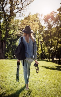 Woman take picture with professional camera on tripod in the summer park