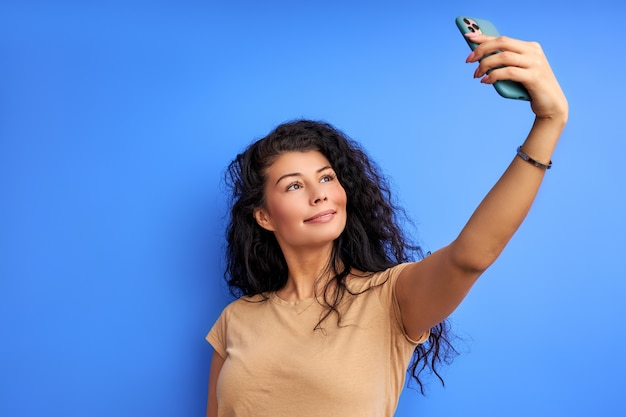 Woman take selfie on phone, looking up at smartphone. isolated on blue wall