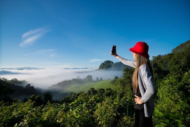 Женщина делает селфи в тумане с видом на горы, пейзаж в провинции мэхонгсон, таиланд.