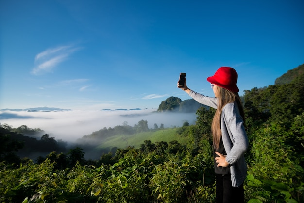 Woman take selfie photo in the mist with mountain views , landscape at mae hong son province, thailand.