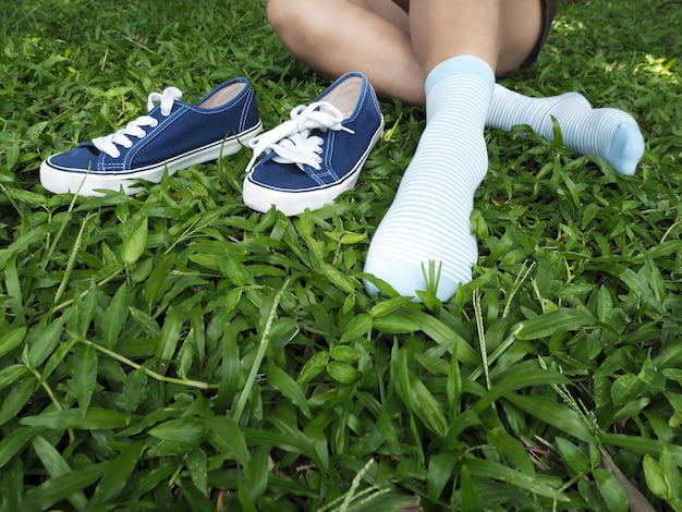Woman take shoe off sitting on green grass in the park.