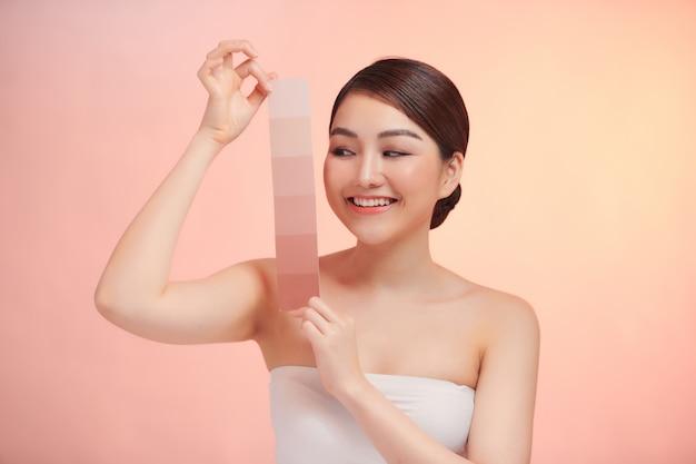 Женщина берет шкалу цвета кожи на фоне biege