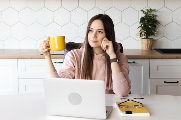 女性は仕事から休憩し、お茶を飲む、ラップトップでオンライン作業