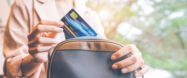 여자는 구매를 위해 주머니에서 신용카드를 꺼냅니다. 웹 배너용입니다. 프리미엄 사진