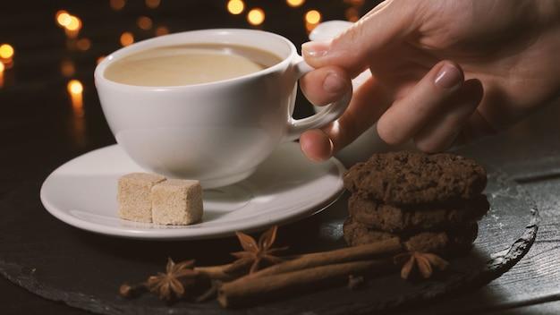 Женщина берет чашку кофе и пьет концепцию рождественского кафе со специями