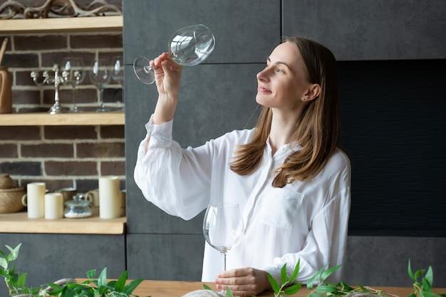 Женщина достает стакан из посудомоечной машины, стоя на кухне